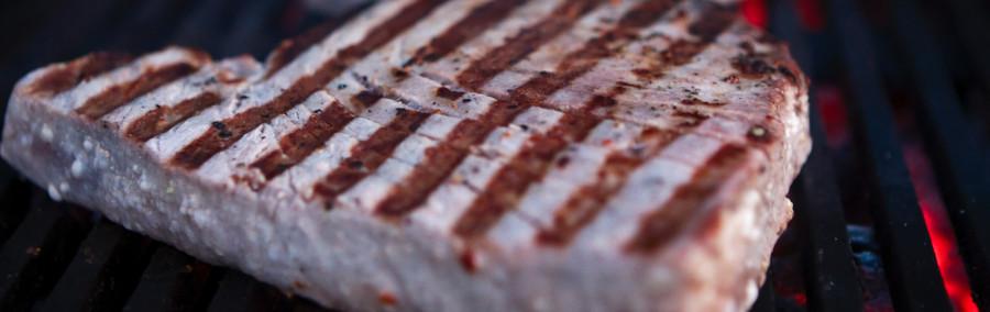 Tunsteaks bliver hurtigt vendt på en super-varm grill